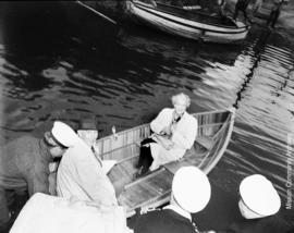 Man and woman being ferried across a small canal